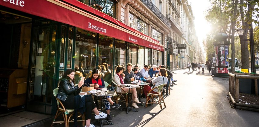 People relaxing, eating and drinking in restaurant in Paris, France