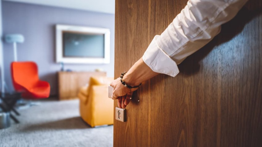 Man hand opening the door of the luxurious hotel room