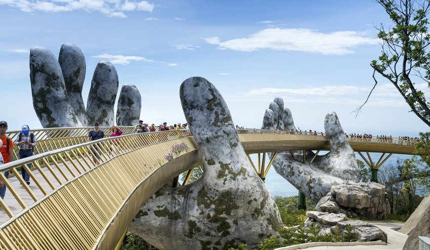 Tourists walk across the Golden Bridge at Ba Na Hill, Vietnam
