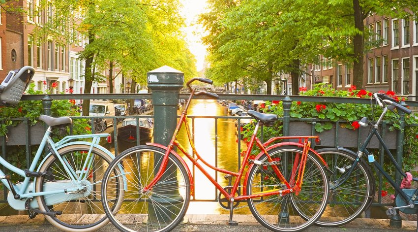 bikes leaning against railing on canal in amsterdam
