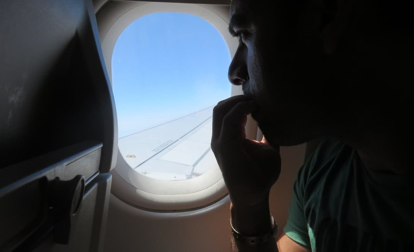 person on plane looking out window