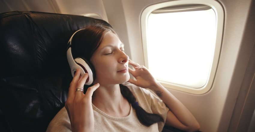 woman wearing headphones on plane