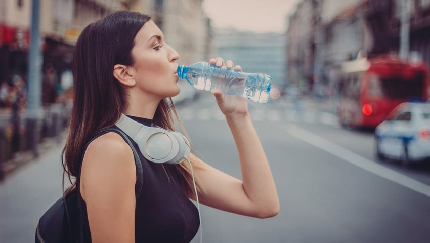 woman drinking water from water bottle