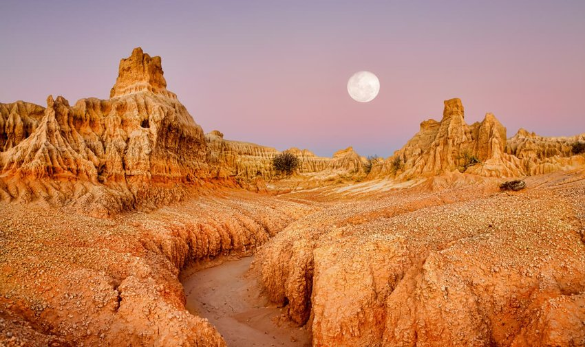 Full moon over desert landscape dawn