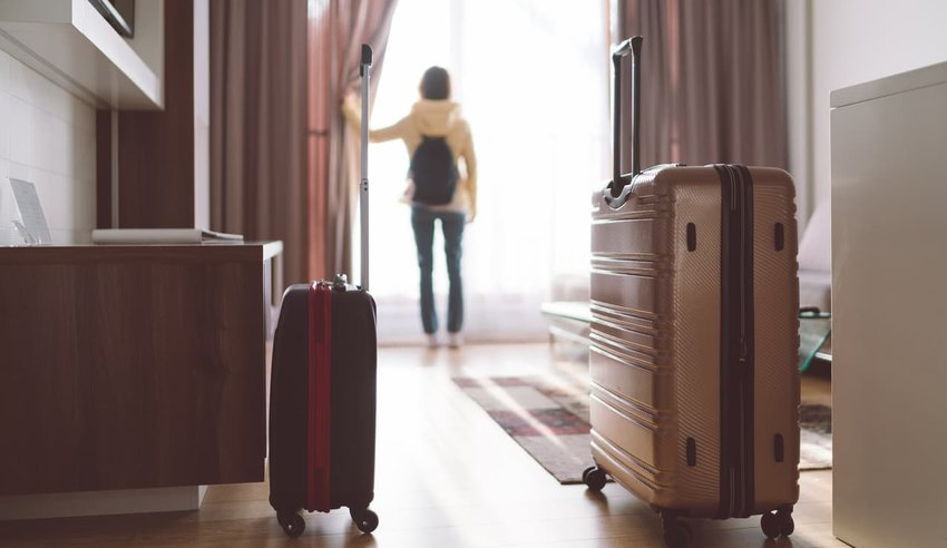 woman with luggage in hotel room
