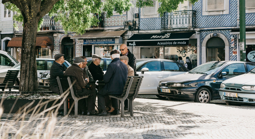 Older men locals sit on a bench and communicate in Lisbon in Portugal