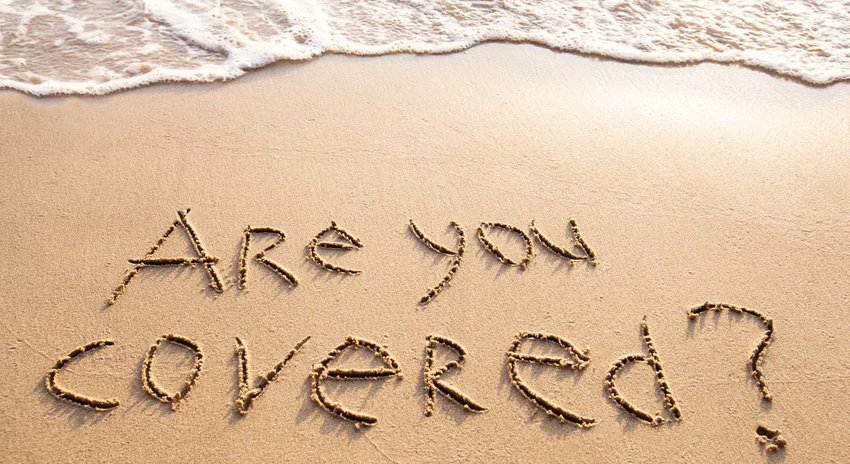 Are you covered travel insurance concept written in sand