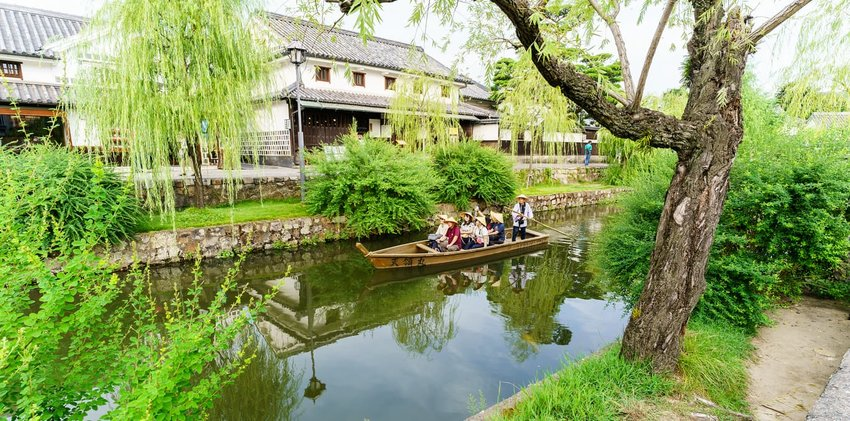 Tourists are enjoying with the old-fashioned boat along the Kurashiki canal in Kurashiki city.