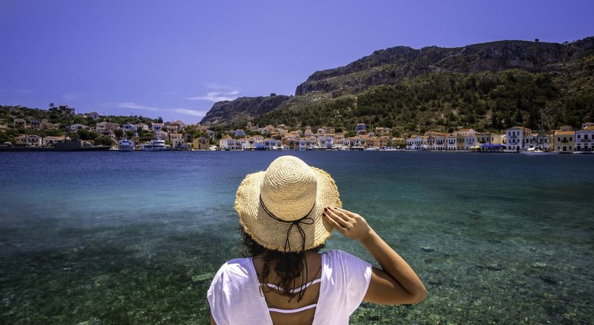 woman looking at Greek Islands across the water