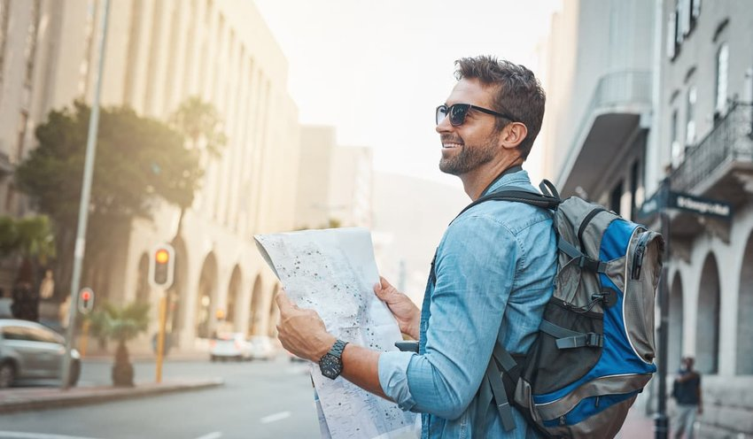 tourist wearing backpack holding map