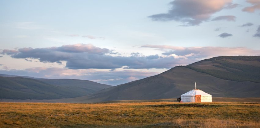 Traditional Mongolian ger on a mountain backdrop in sunset light