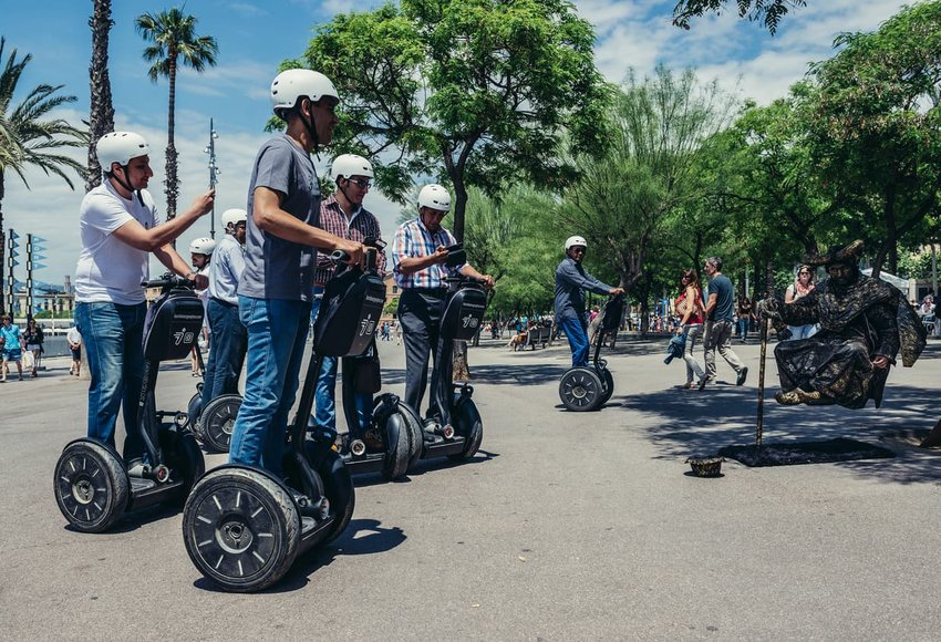 Segway trip participants looks at street performer