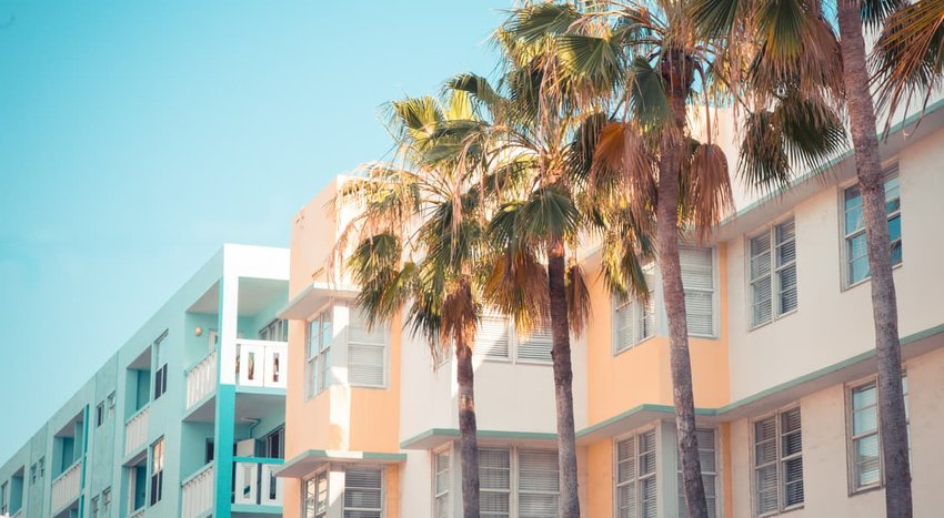 Typical pastel-colored 1930s Art Deco architecture with palm trees in Miami, Florida