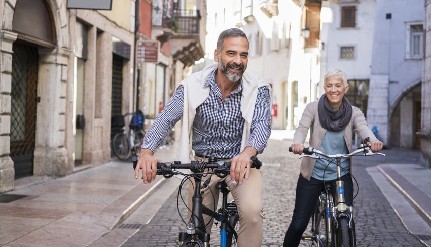 older couple exploring a european city by bike
