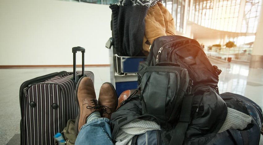man who has a lot of bags, sits waiting at the airport