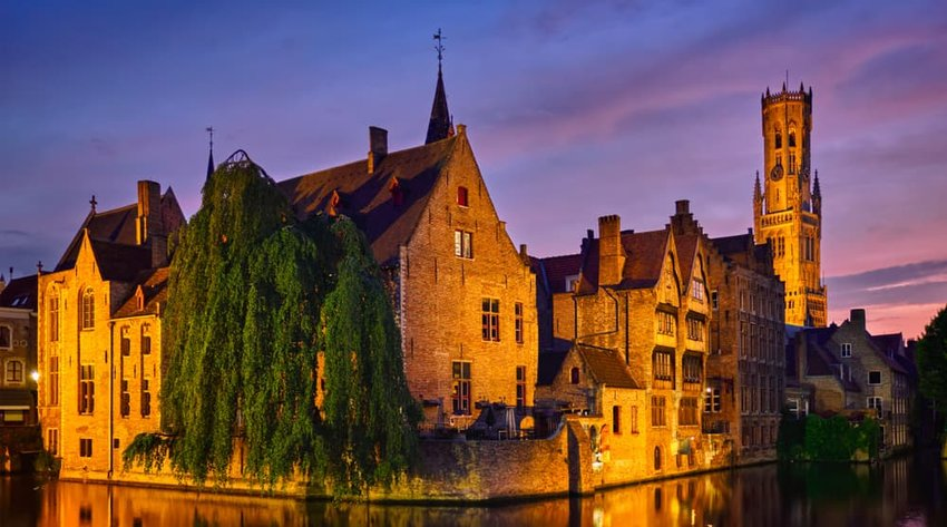 Rozenhoedkaai canal with Belfry and old houses along canal with tree in the night. Brugge, Belgium
