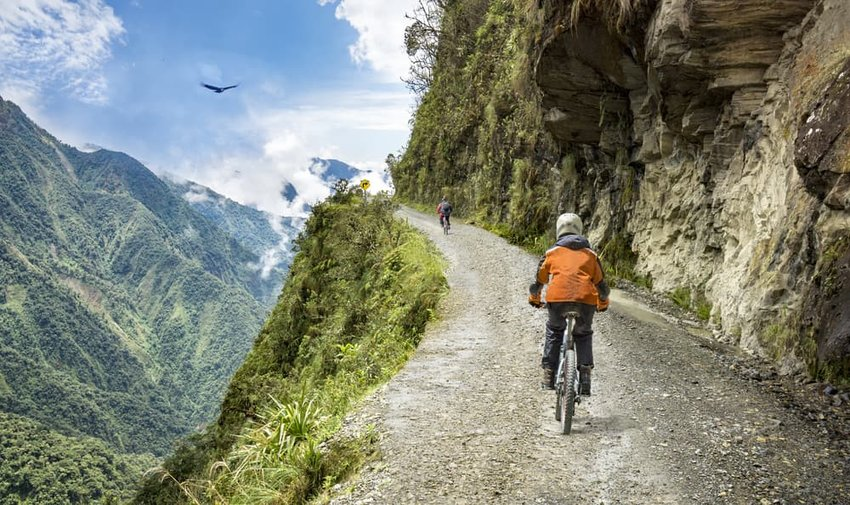 "Bike tourists ride on the ""road of death"" downhill track in Bolivia."