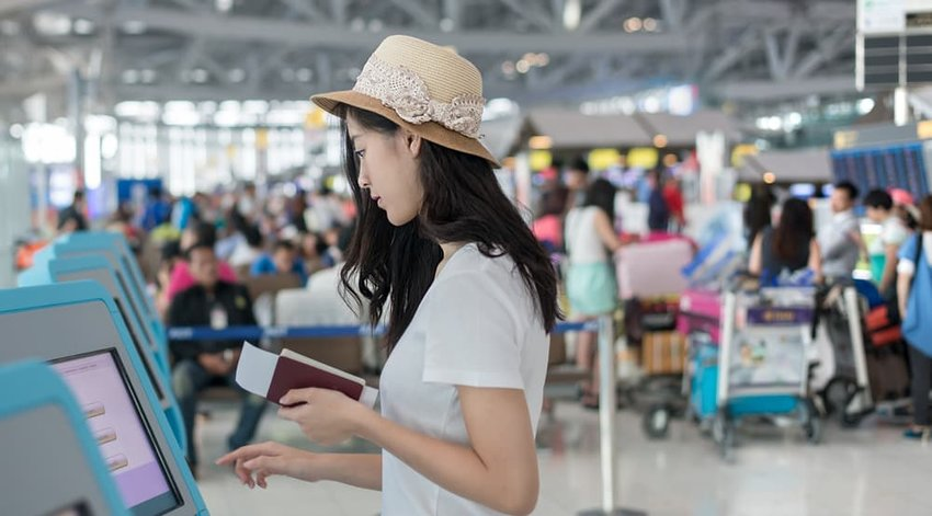 Young woman using self check-in kiosks in airport
