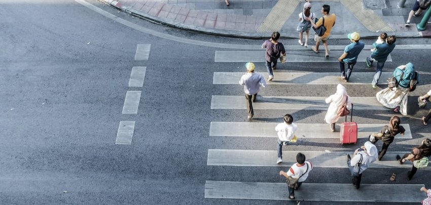Blur people are moving across the pedestrian crosswalk in the city road