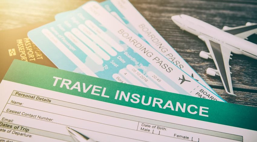 Booking travel insurance with model plane on wooden background