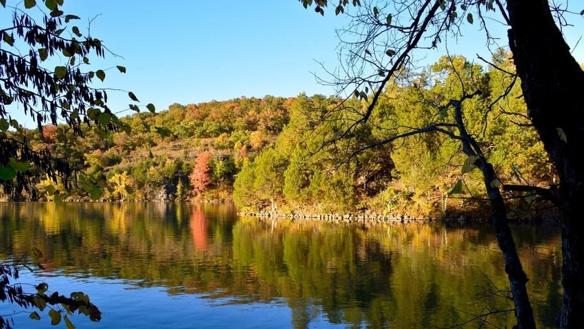 The autumn forest is reflected on the water. Lake of the Ozarks, Missouri