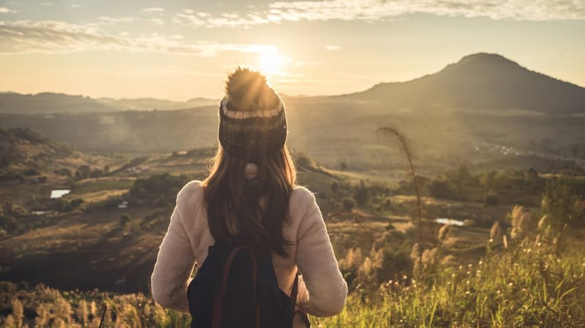 young woman traveler watching the sunrise over mountains