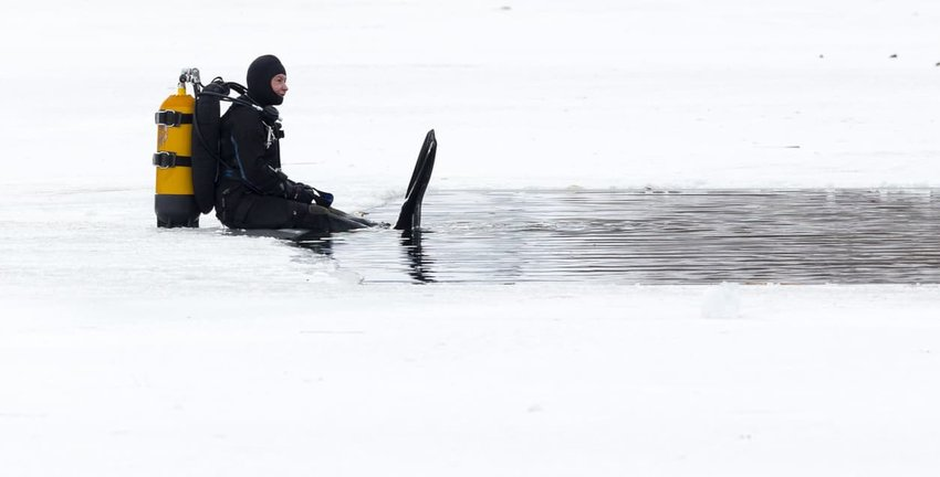 under ice diver waiting to submerge in water