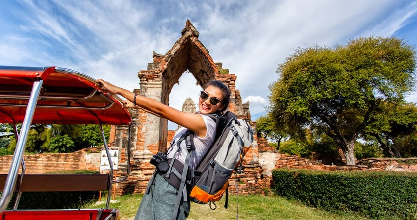 Young female traveler with backpack traveling while standing on Tuk Tuk