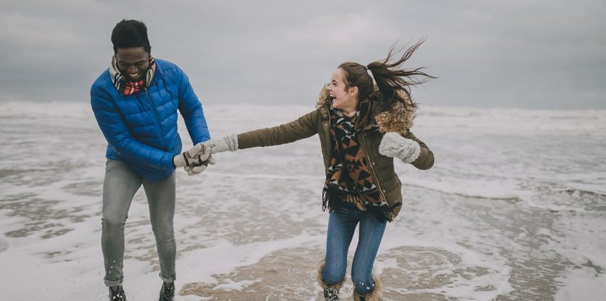 Young Couple Laughing In The Winter Beach Sea