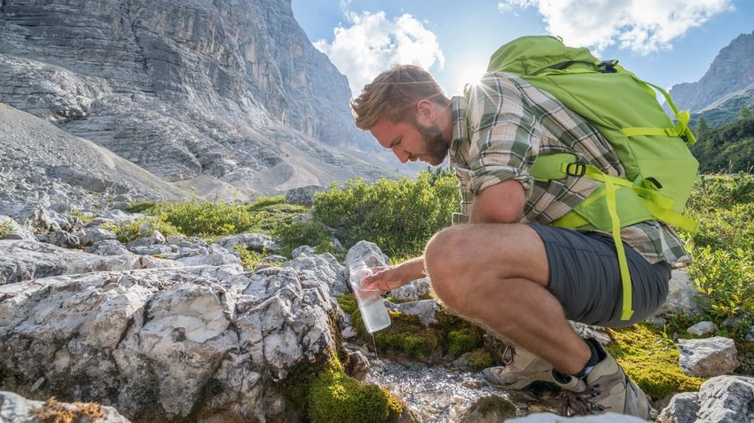 Hiker filling water bottle from stream on mountain trail, Dolomites, Italy