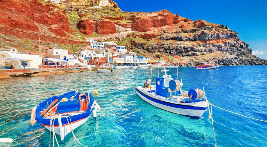 beautiful landscape of two fishing boats anchored to quay at the old port panorama in Oia Ia village on Santorini Greek island in Aegean sea
