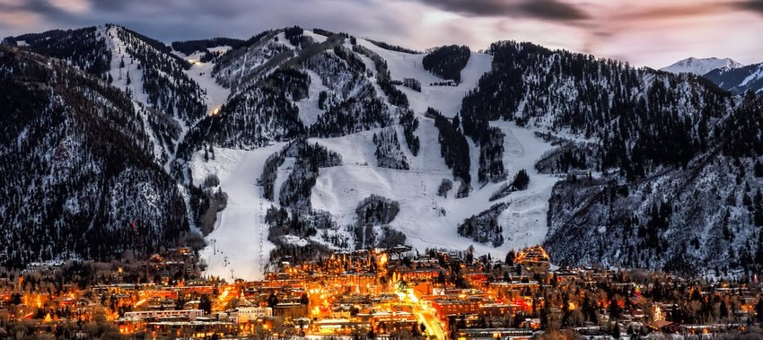 Aspen at night backed by snow covered mountains
