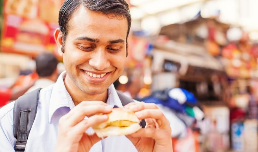young indian man eating veda pav on the street
