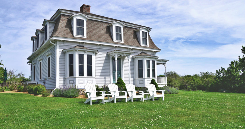 A horizontal image of a classic beach house, with a Mansard roof, on windswept Block Island.