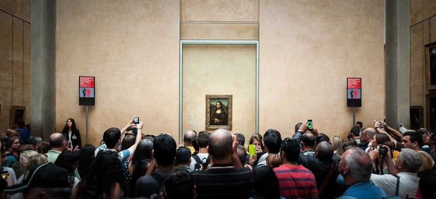 crowds gather in front of the mona lisa at the lourve in paris