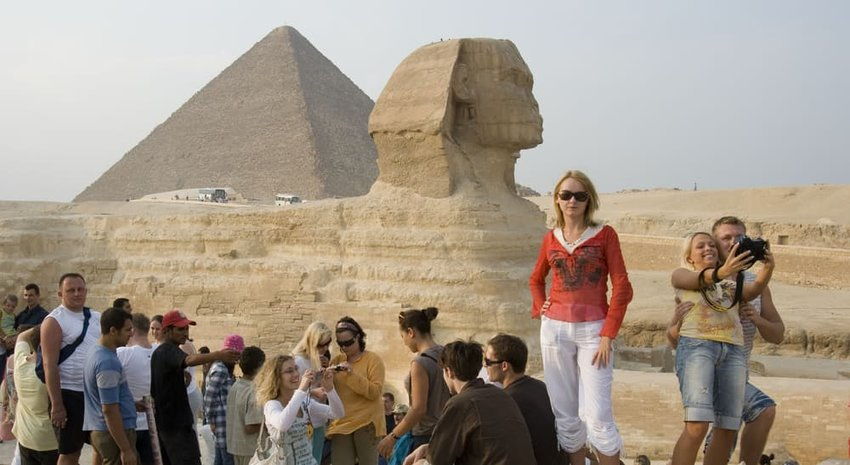 Many joyful tourists are photographed near the pyramids and the Sphinx in Egypt
