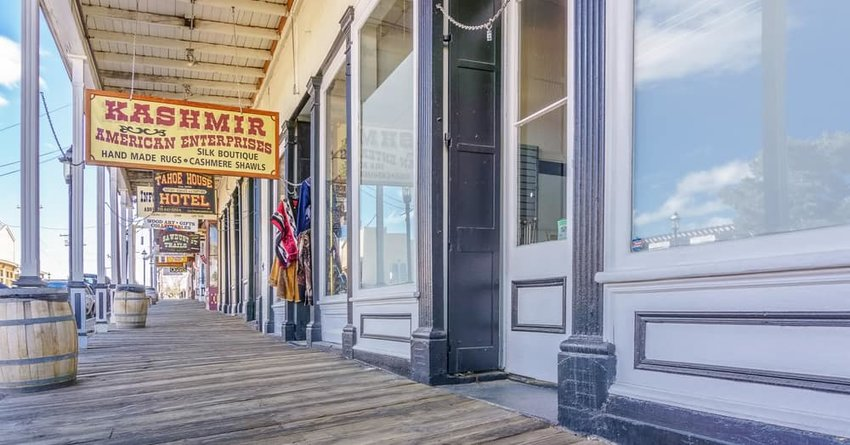 Street scene of a wooden boardwalk and vintage signage of retail establishments in historic Virginia City.