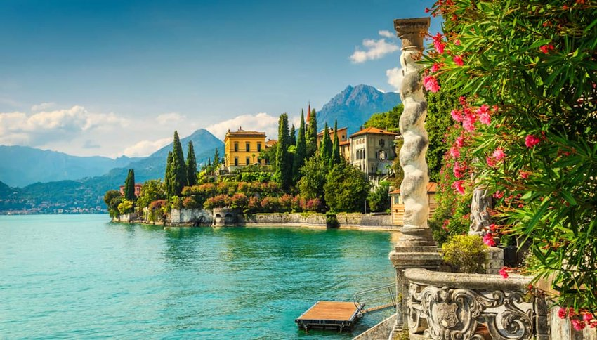 Photo of Lake Como shoreline with mountains in the distance