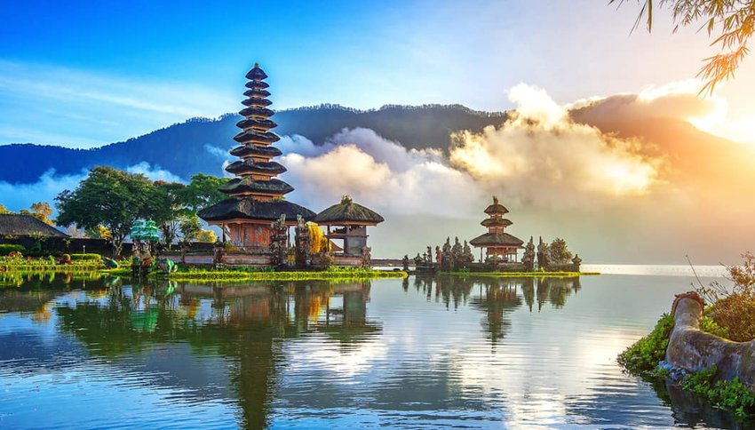 Photo of Bali temples on a lake, with mountains in the distance