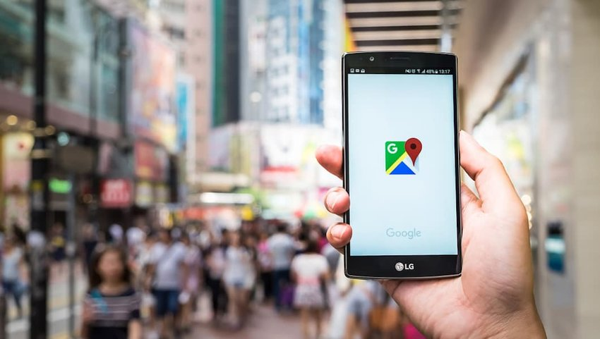 Photo of the Google Maps logo on a phone with a cityscape in the background