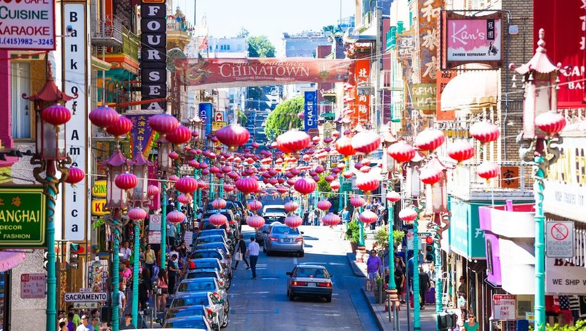 View of the main street of he chinatown district, traffic of cars and people.