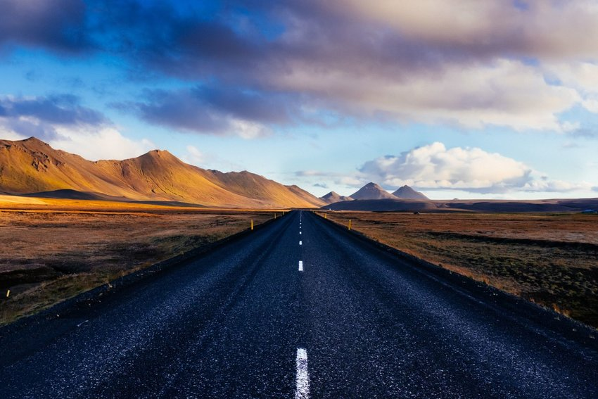 Empty Icelandic road leading to mountains