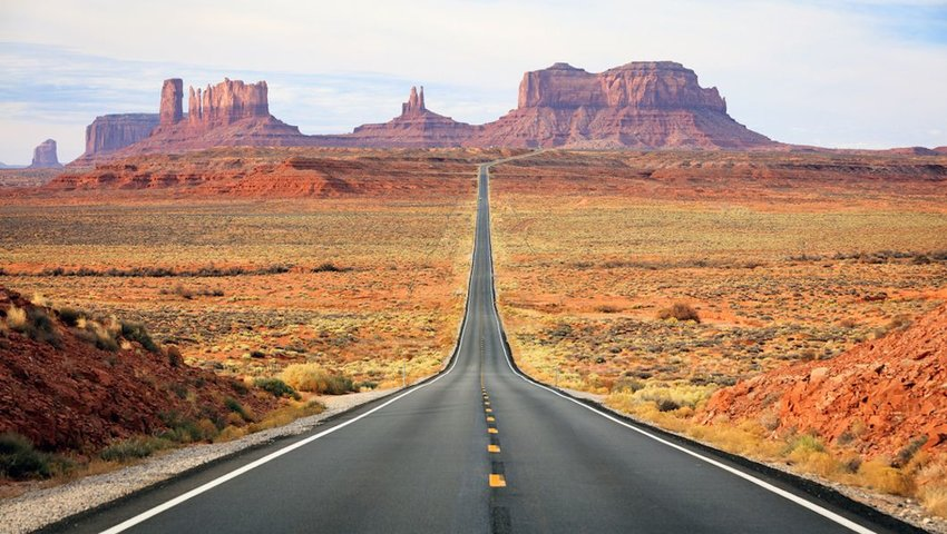 Photo of a road leading off into the distance, with red rocks towering in the sky