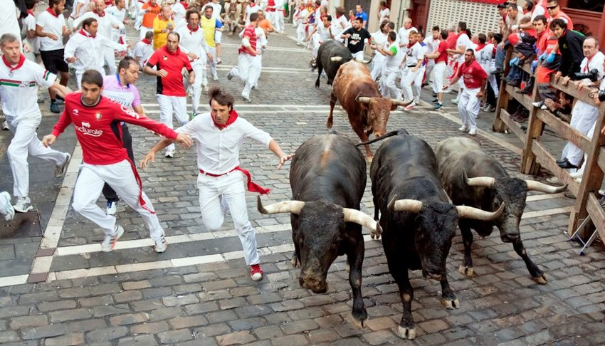 men run from bulls in street Estafeta during San Fermin festival in Pamplona