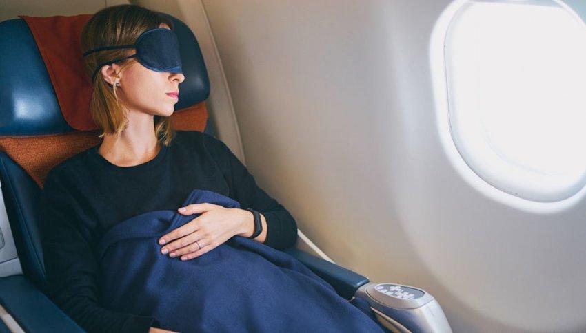 Woman sleeping on plane with eye mask