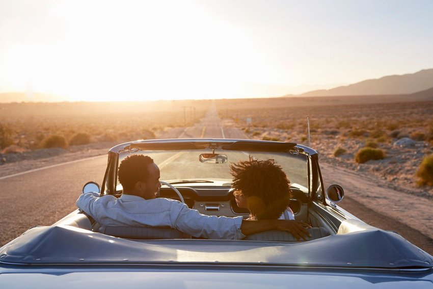 Photo of a couple in a convertible, driving on an open road