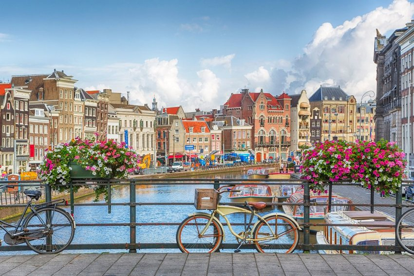 Photo taken on a bridge in Amsterdam, with bikes in the foreground and buildings in the background