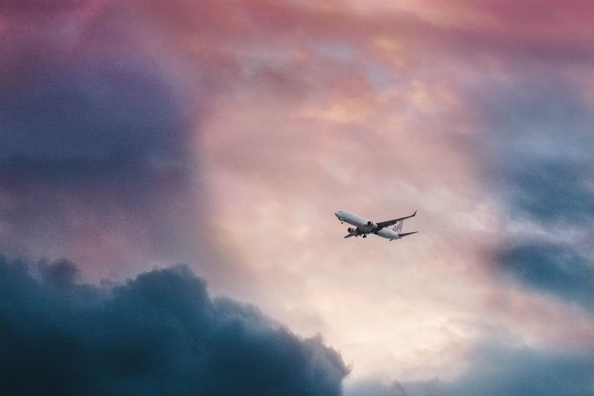 Plane flying through a break in clouds at sunrise