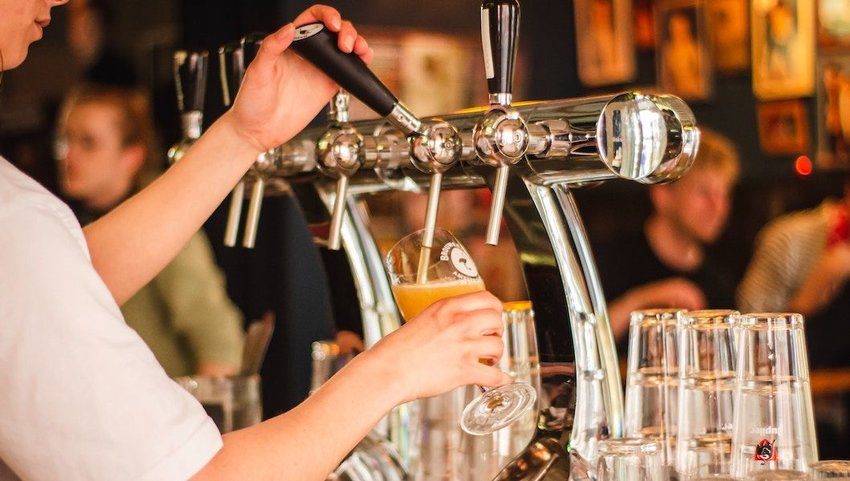 Bartender pouring a glass of beer at a bar.