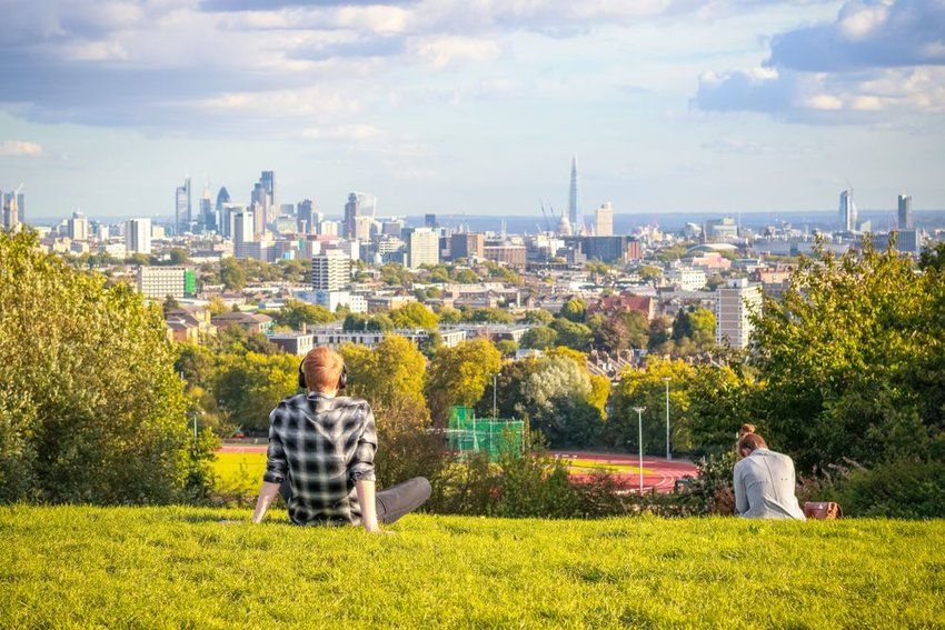 Tourists looking over London city skyline from Parliament Hill in Hampstead